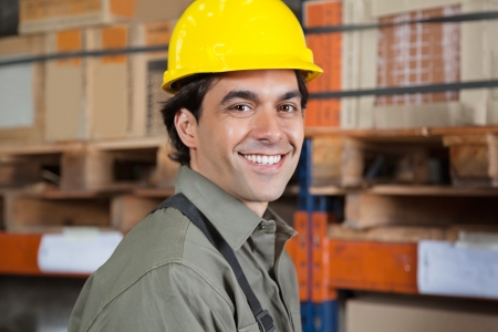 Portrait of happy young foreman in hardhat at warehouse photo