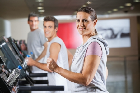 Portrait of happy mature woman and men running on treadmill in fitness center photo