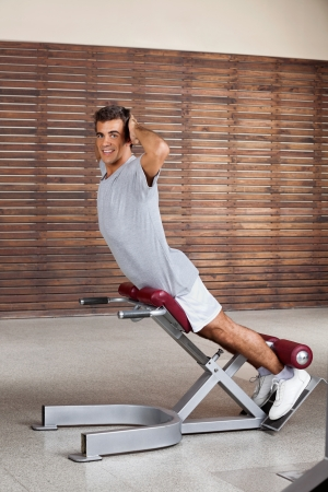 lower body: Portrait of young man exercising on machine in health club