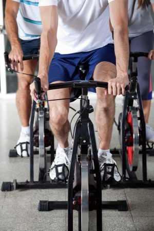 Low section of three people on exercise bikes in health club photo