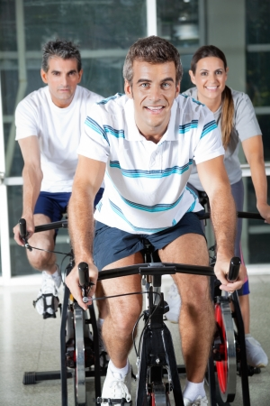 Portrait of happy men and woman on exercise bikes in health club photo