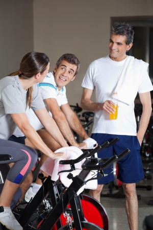 Happy friends talking during work out in health club photo