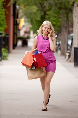 Attractive young blond woman walking down street talking on cell phone photo