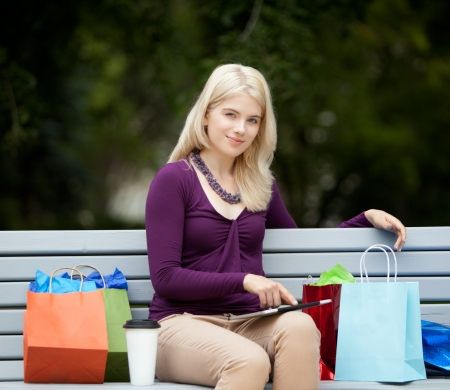 Pretty young female on city shopping trip taking a rest on bench with a digital tablet Stock Photo - 16085845