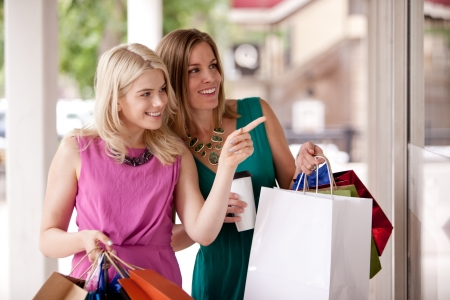 chicas de compras: Dos mujeres bastante ventanas de compras en una ciudad centro de la ciudad Foto de archivo