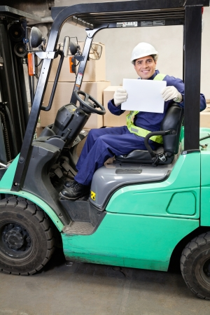 Portrait of forklift driver displaying blank placard photo
