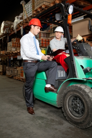 Supervisor showing clipboard to forklift driver at warehouse photo