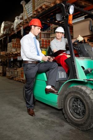 istruzione: Supervisore mostrando appunti a carrelli elevatori autista a magazzino