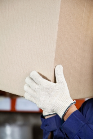 Foreman s hands lifting cardboard box at warehouse photo