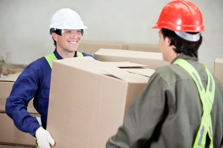 Two foremen carrying cardboard box at warehouse photo