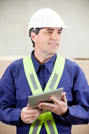 Warehouse worker with digital tablet standing in warehouse photo