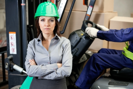 Portrait of confident female supervisor with man driving forklift in warehouse photo