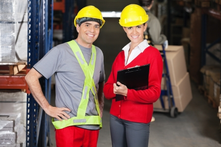 Portrait of young female supervisor holding clipboard standing with foreman in warehouse photo