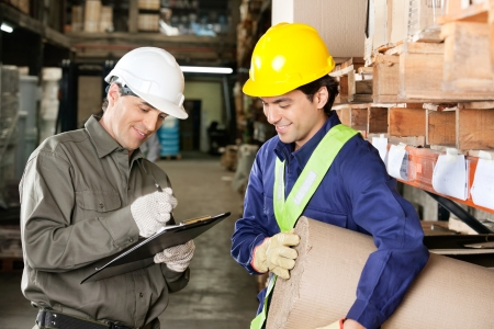Young foreman looking at supervisor writing notes in warehouse Stock Photo - 16085803