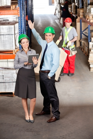 sack truck: Female supervisor and male colleague using digital tablet with foreman working at warehouse Stock Photo