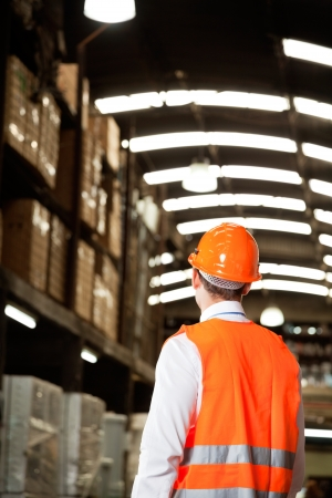 Rear view of male supervisor wearing protective vest and helmet at warehouse Stock Photo - 16085826