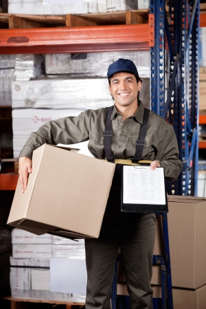 Portrait of young male supervisor holding clipboard and cardboard box at warehouse Stock Photo - 16085830