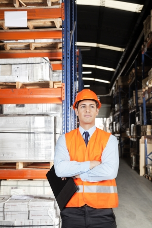 Confident young male supervisor in orange protective vest with arms crossed at warehouse Stock Photo - 16085841