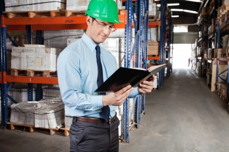 Young male supervisor reading book at warehouse Stock Photo - 16085799