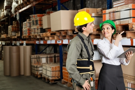 Female supervisor with foreman pointing at stock on shelves in warehouse photo