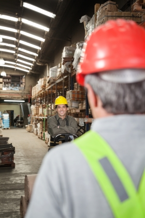 Portrait of young foreman with arms crossed standing at warehouse photo
