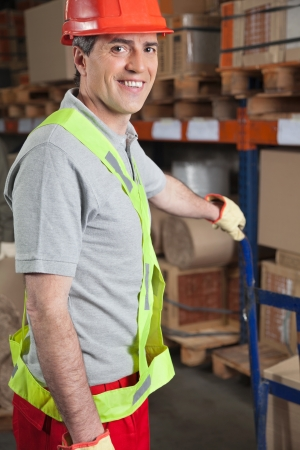 Portrait of happy mid adult foreman holding handtruck at warehouse photo