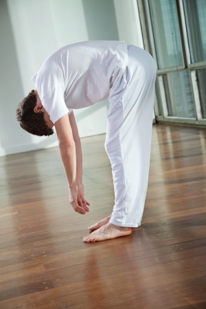 Full length of a young man practicing yoga called Standing Forward Bend at gym photo
