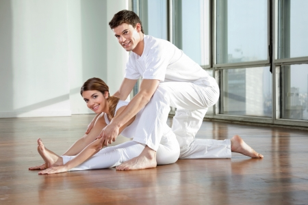 Portrait of young woman learning yoga exercise from male instructor at gym photo