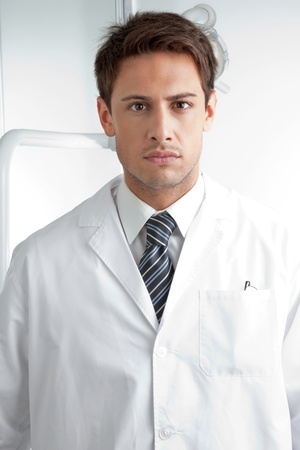 Portrait of serious male dentist wearing labcoat in clinic photo