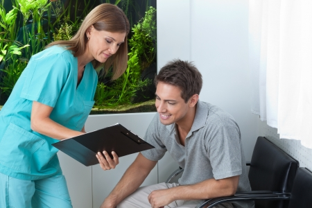 Female dentist showing something to male patient on clipboard at clinic photo