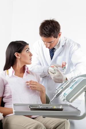 Male dentist using teeth model while explaining dental procedure to patient photo