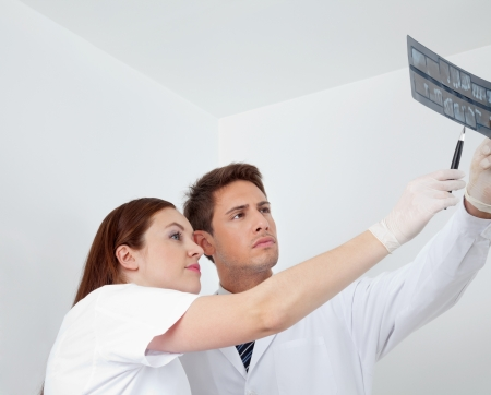hygienist: Dentist with female nurse analyzing patient s X-ray report in clinic