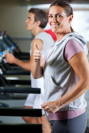 Side view of happy mature woman and man running on treadmill in health club photo