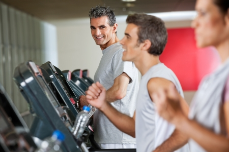 Portrait of happy mature man running on treadmill in fitness club photo