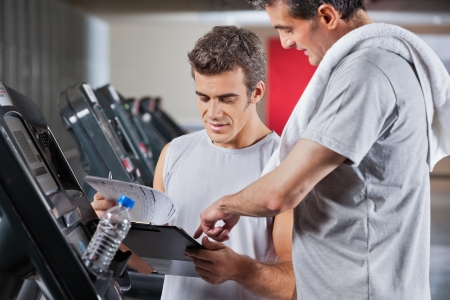 Instructor guiding man to fill the membership form of health club photo