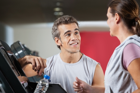 Happy male instructor looking at female client exercising on treadmill in health club photo