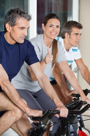 Portrait de femme mature heureux montrant thumbs up signe pendant l'exercice avec des amis sur le vélo tourne dans un club de santé