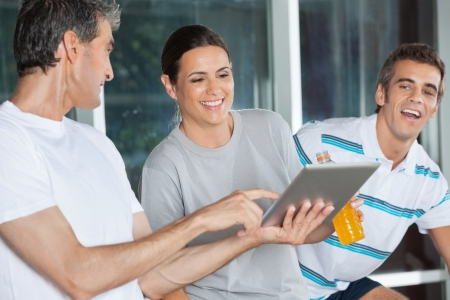 Happy friends using digital tablet in health club photo
