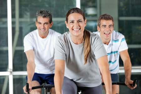 Happy men and woman on exercise bikes in health club photo