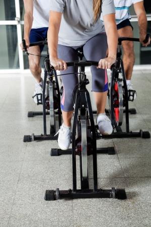 Low section of people on exercise bikes in health club photo