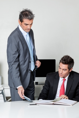 Businessmen calculating finances at desk in office Stock Photo - 16120061
