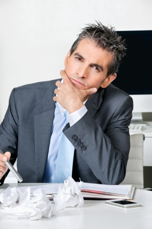 Portrait of thoughtful businessman sitting at desk in office photo