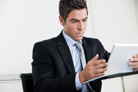 Handsome young businessman using digital tablet in office Stock Photo - 16120060