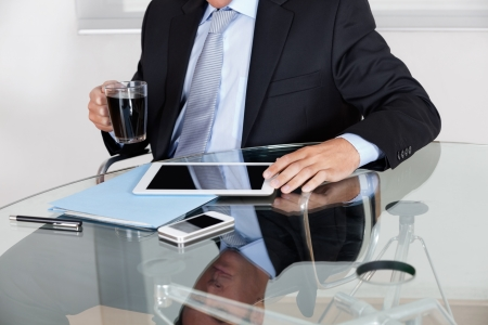 Midsection of young businessman with coffee cup using digital tablet at desk in office photo