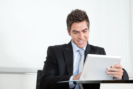 Handsome young businessman using digital tablet at desk in office Stock Photo - 16120053