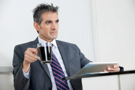 Mid adult businessman with coffee cup using digital tablet at desk in office Stock Photo - 16120062