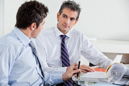 Businessmen discussing paperwork in a meeting at office photo