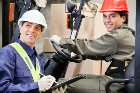 lift truck: Portrait of young forklift driver with supervisor writing notes at warehouse