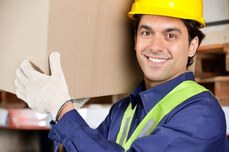 Portrait of a young warehouse worker carrying cardboard box photo