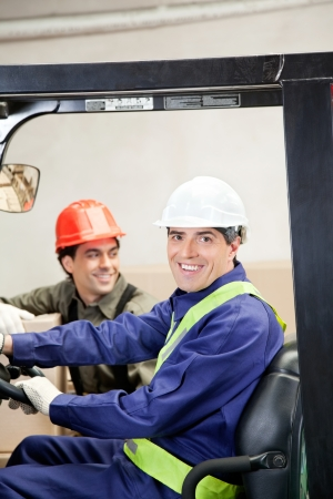 Portrait of happy forklift driver with colleague at warehouse photo